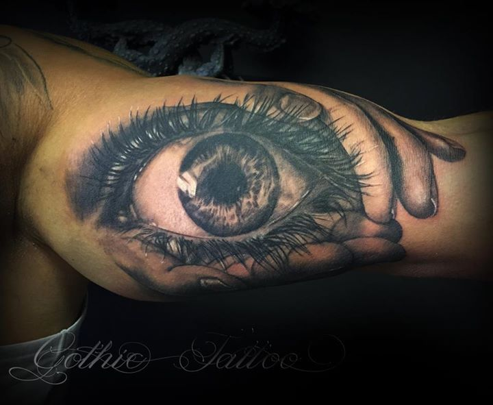 Black & white Eye held in hands tattoo on bicep by Gothic Tattoo, UK