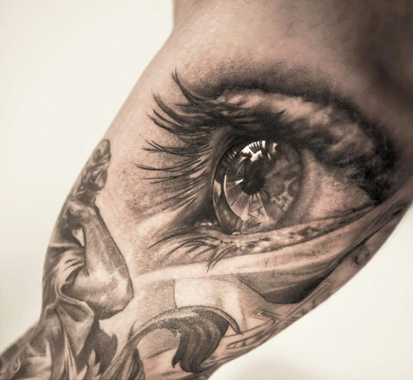 Awesome eye tattoo on bicep by Niki Norberg