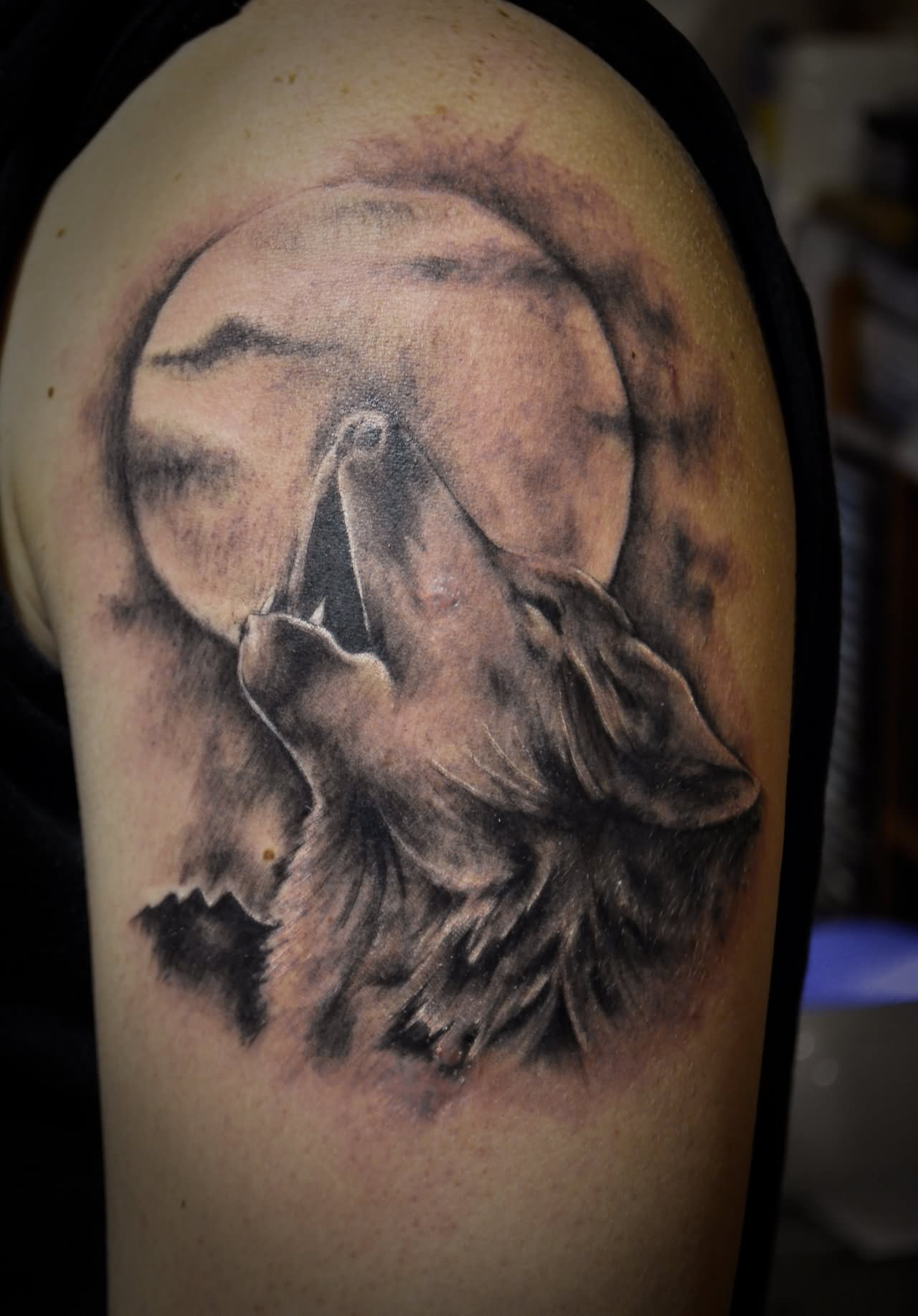 Howling wolf and moon tattoo on half sleeve