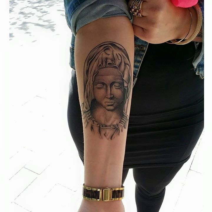 Virgin Mary statue tattoo on forearm by Didson Scripts