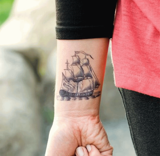Black And Grey Ship On Ocean Tattoo On Wrist