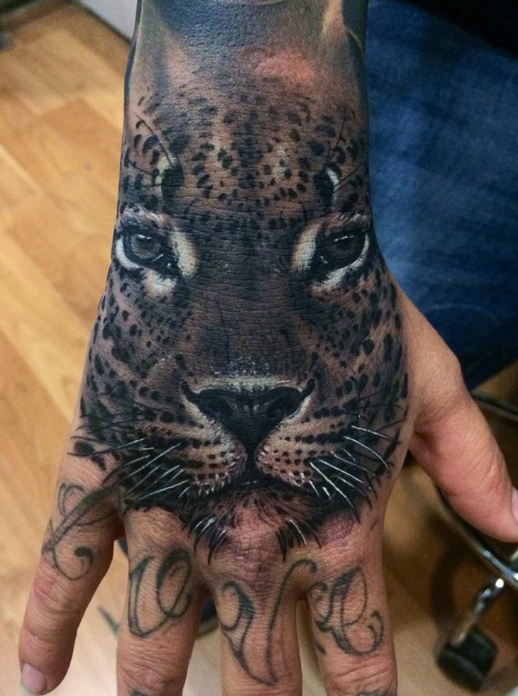 Black leopard face tattoo on hand for Animal hand tattoos