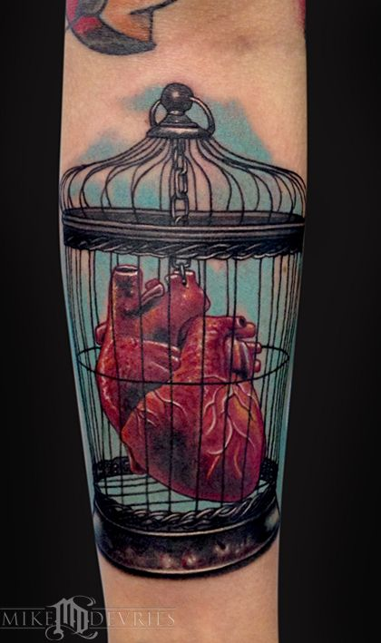 Caged real human heart tattoo on arm