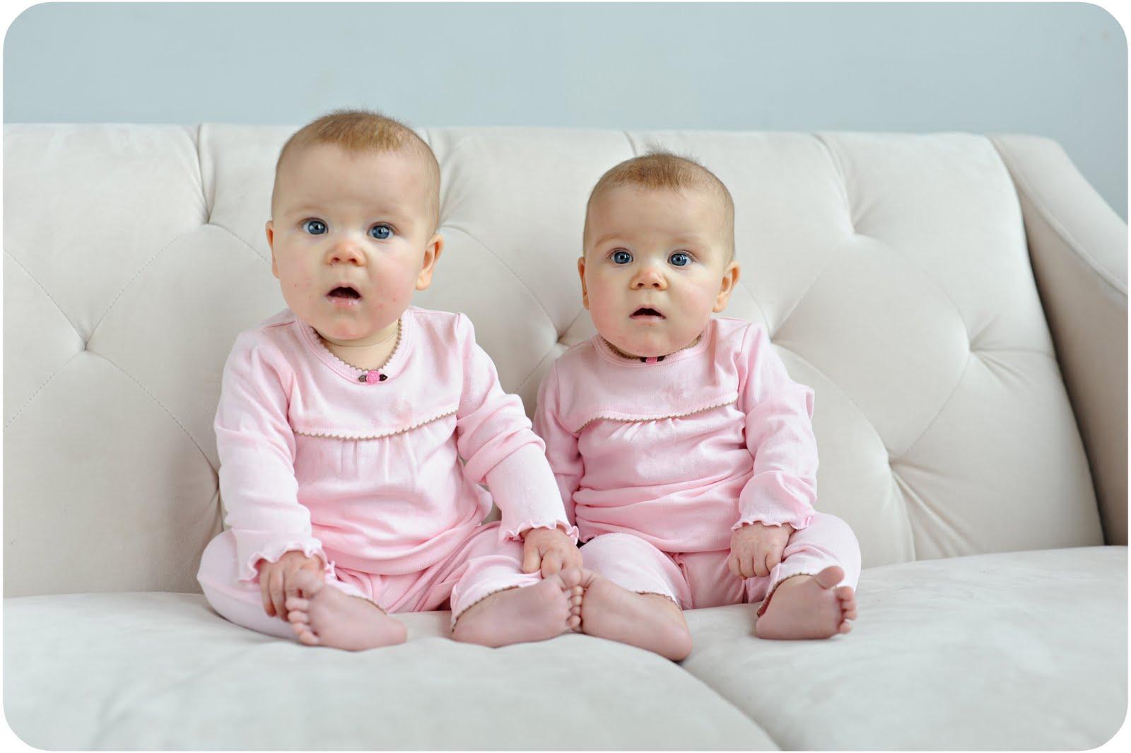 Cute twin babies sitting on sofa