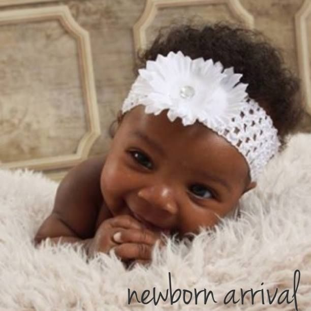 Newborn black baby with white headband
