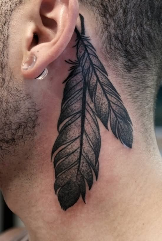 Black And Grey Two Feather Tattoo On Man Behind The Ear