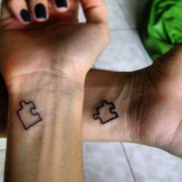 black puzzle tattoo on couple wrist