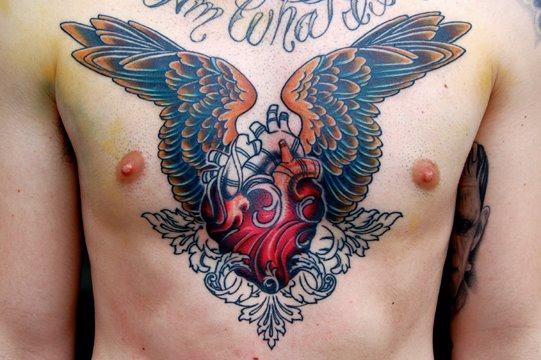 Colorful Real Heart With Wings Tattoo On Man Chest