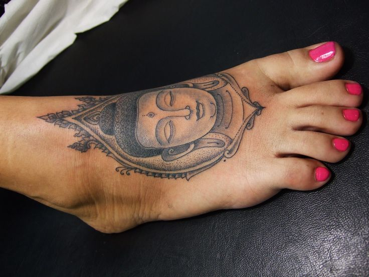 Black And Grey Buddha Face Tattoo On Girl Foot