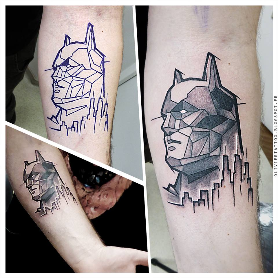 Black and grey geometric batman face tattoo on forearm