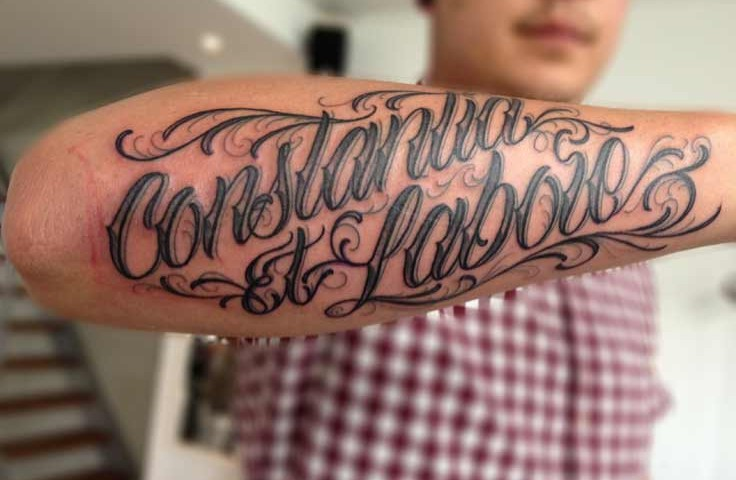 Black Constantia Et Labore Lettering Tattoo On Forearm