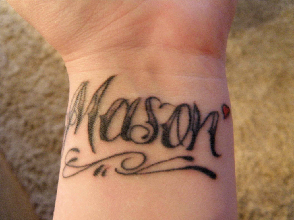 Black Ink Mason Lettering With Tiny Red Heart Tattoo On Wrist