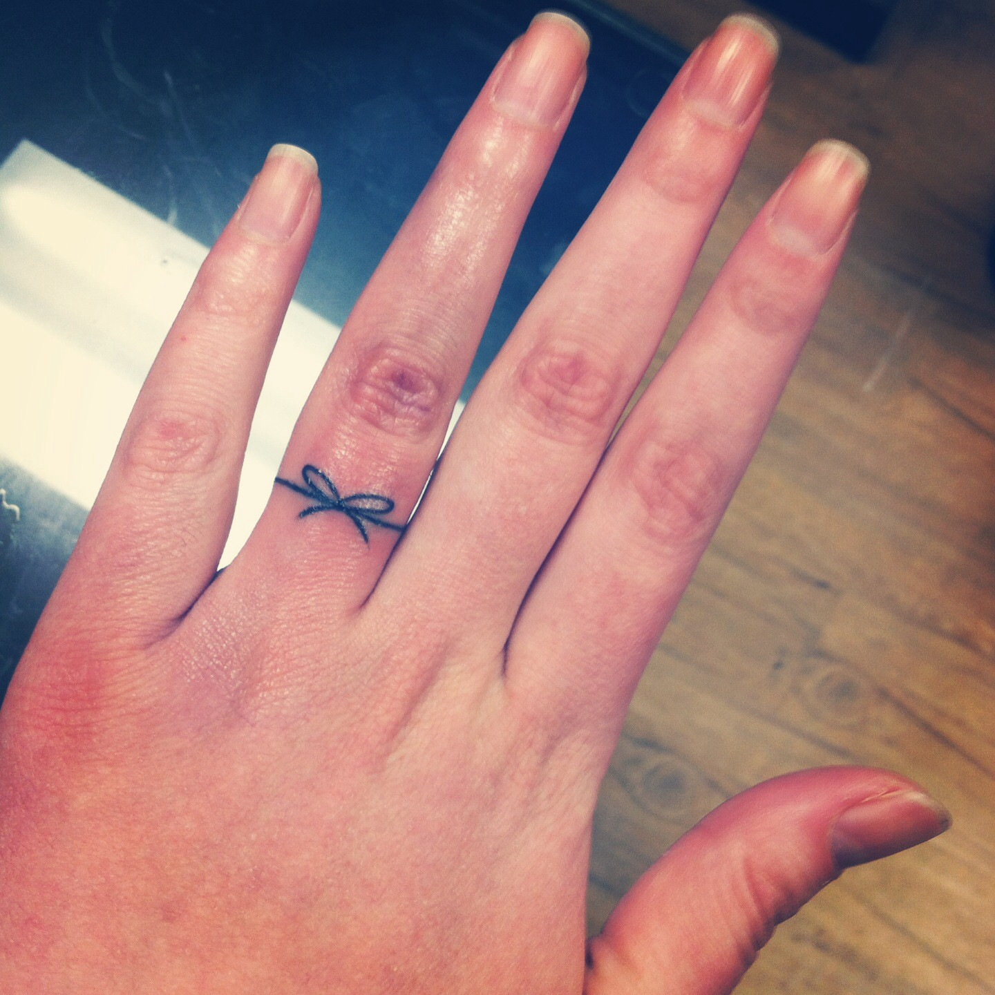 Black Thread Bow Wedding Ring Tattoo On Girl Finger