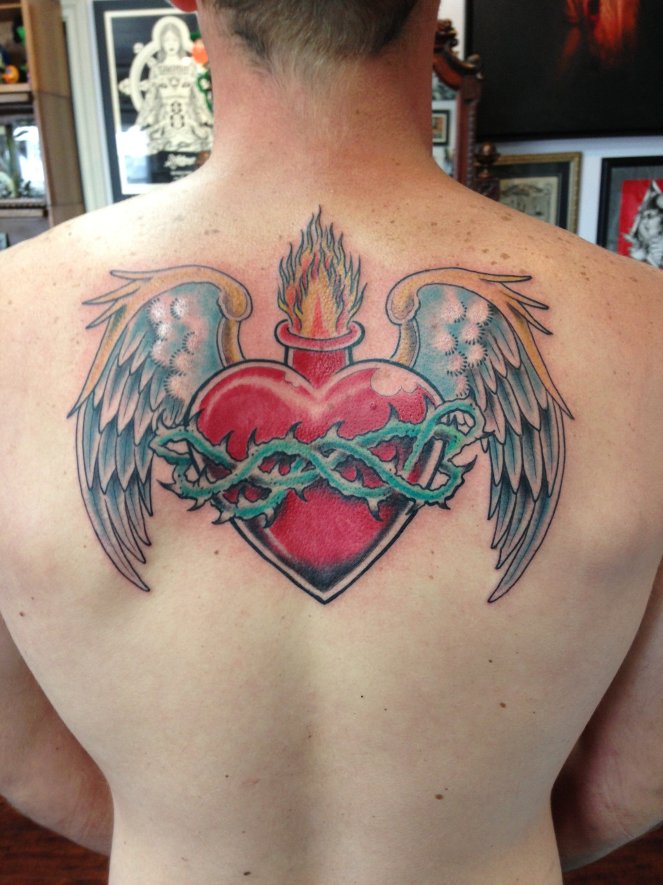 Sacred Heart With Wings Tattoo On Man Upper Back