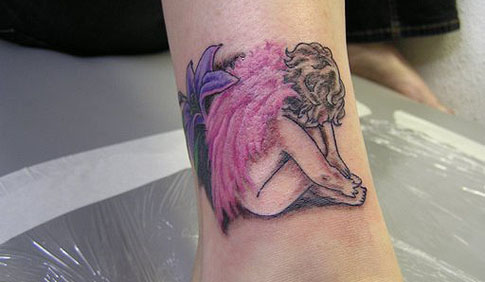 Small crying baby angel with pink wings tattoo on leg