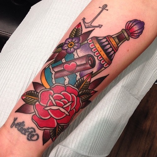 Traditional Scroll In Bottle With Flowers Tattoo On Forearm By