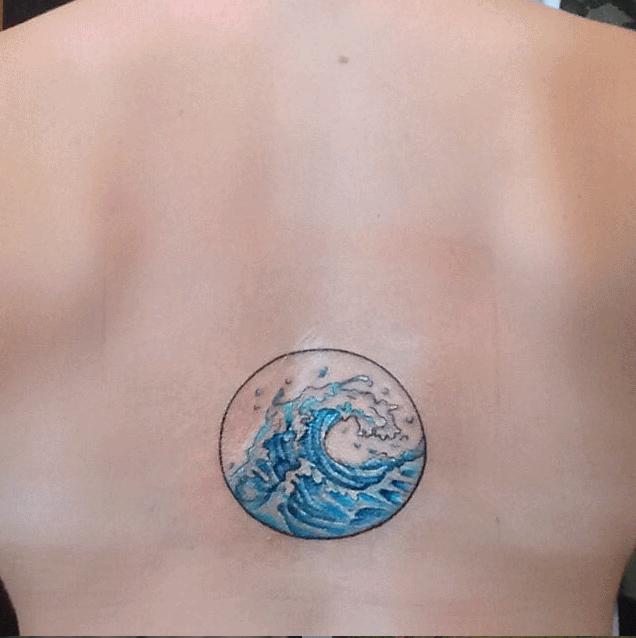 Blue Ink Wave In Circle Frame Tattoo On Upper Back