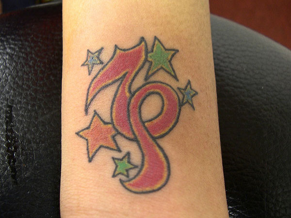 8f7783f987a6f Colored Stars And Capricorn Tattoo On Forearm
