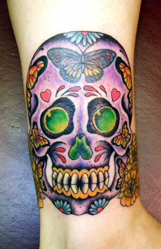 Dia de los muertos skull with flowers tattoo on upper back for Dia de muertos tattoos