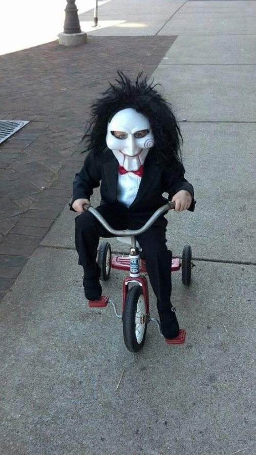 baby in halloween costume riding tricycle funny image