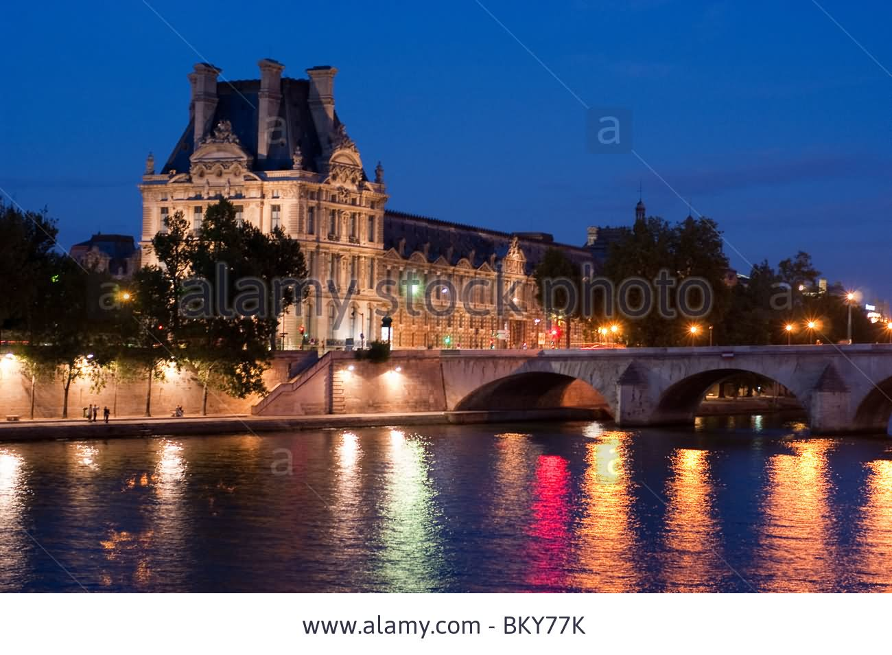 Seine River Lit Up At Dusk With The Louvre Museum