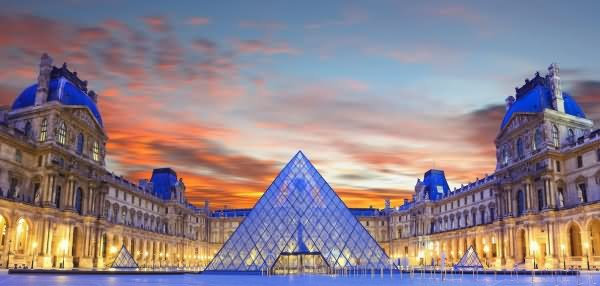 The Louvre Museum And Glass Pyramid At Sunset