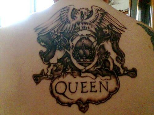 Black Queen Logo Tattoo On Upper Back