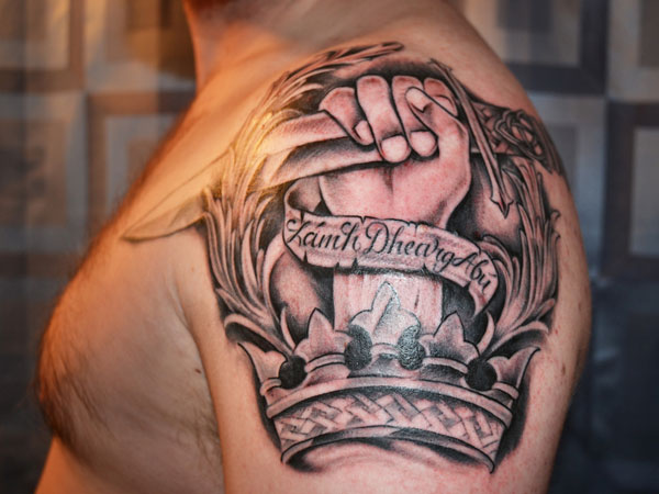 Dagger in hand and crown tattoo on left shoulder for men for Tattoo ideas men shoulder