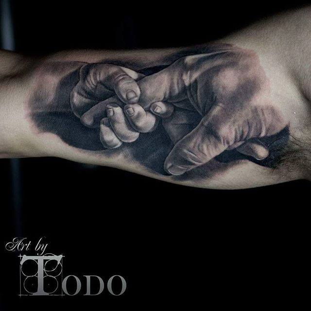 Baby Holding Dad S Finger Realistic Tattoo On Bicep By Todo