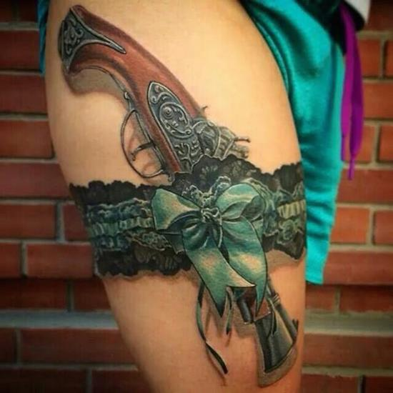 Dark ink revolver garter tattoo on thigh for How to put ink in a tattoo gun