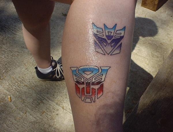 Colorful Two Transformer Logo Tattoo On Leg Calf By Rachel