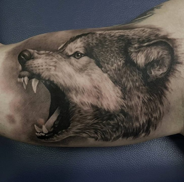 Grey ink angry wolf head tattoo on bicep by casper tattoos for Wolf head tattoos