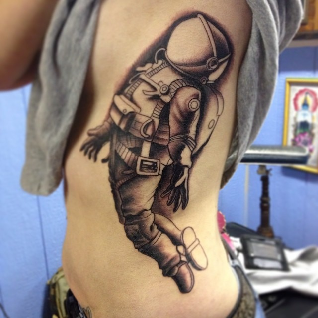 grey ink astronaut tattoo on side rib. Black Bedroom Furniture Sets. Home Design Ideas