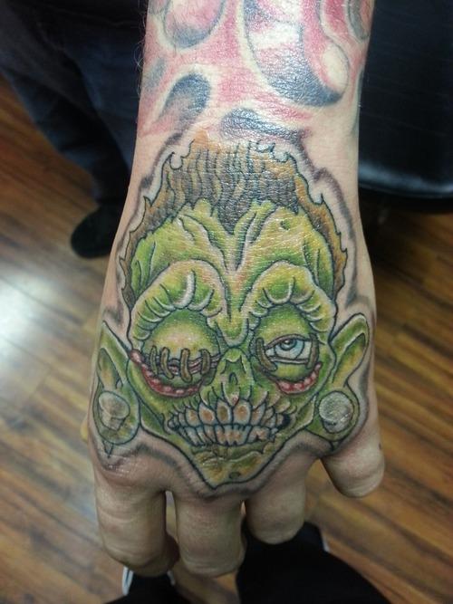 Green ink shrunken head tattoo on left hand for Tattoo shops canton ohio