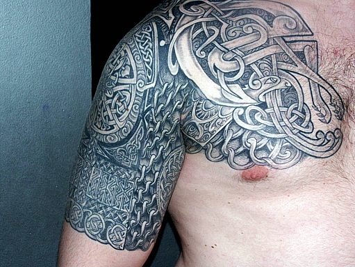 Grey Ink Celtic Tattoo On Chest And Half Sleeve