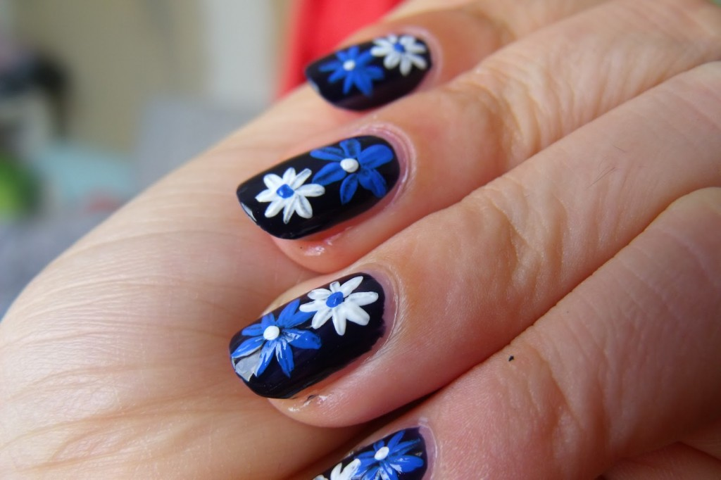 Black Base Nails With Blue And White Acrylic Flowers Design
