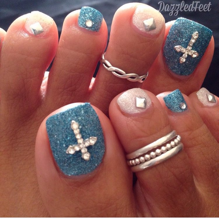 blue and white glitter toe nail art with cross sign
