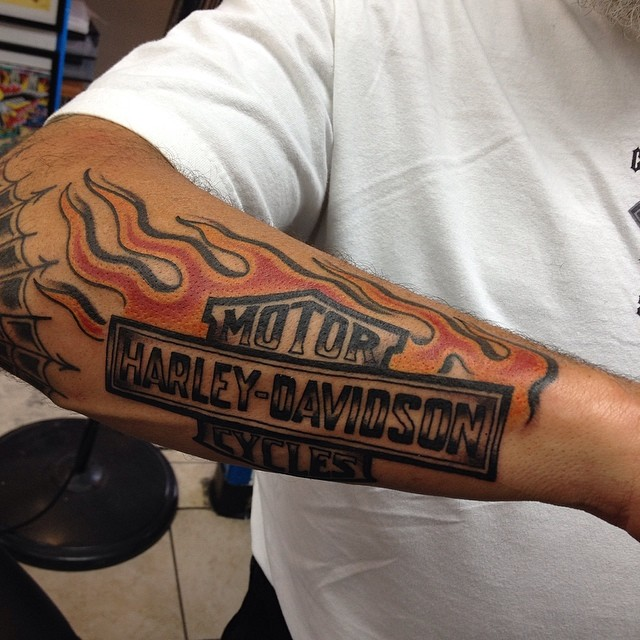 071176812 Flaming Harley Davidson Logo Tattoo On Forearm