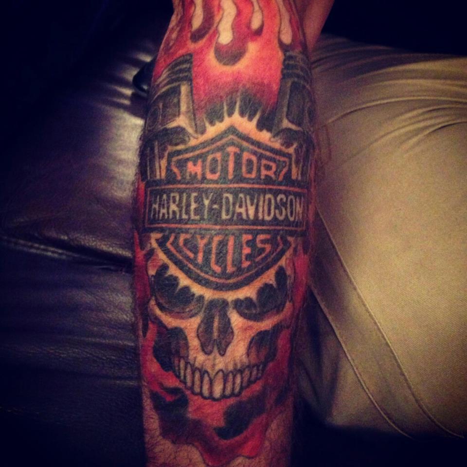Terrific Flaming Harley Logo And Engine Skull Tattoo On Arm