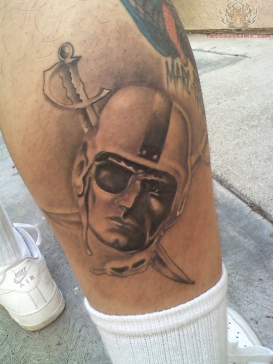 b250d733463cd Grey Ink Crossed Swords And Oakland Raider Face Tattoo On Leg