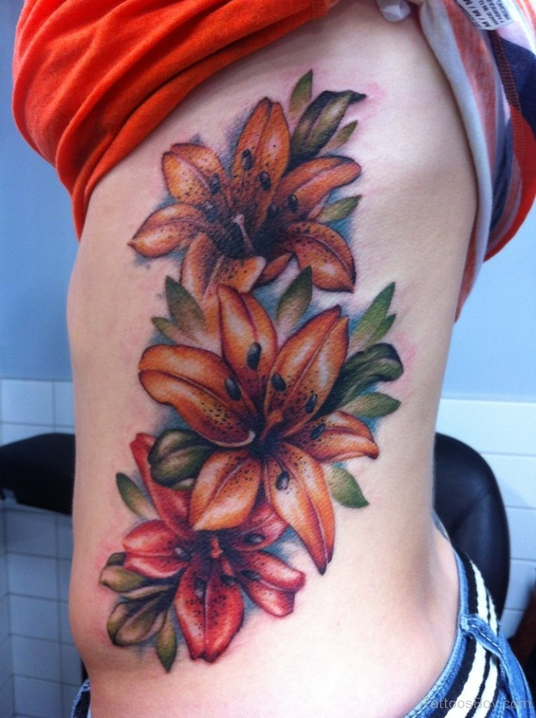 602ce9d077a2a Lily Flowers Colored Tattoo On Rib Cage