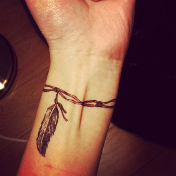 Feather bracelet tattoo on wrist for men for Wrist bracelet tattoos with names