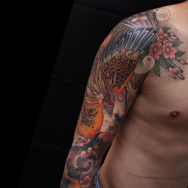 Colorful Phoenix With Flowers Tattoo On Man Right Upper Arm