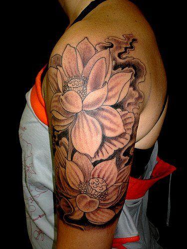 Black Ink Lotus Flowers Tattoo On Left Upper Arm