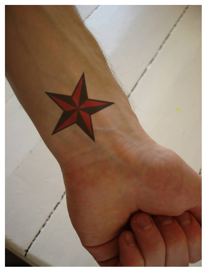 Red And Black Nautical Star Tattoo On Left Wrist