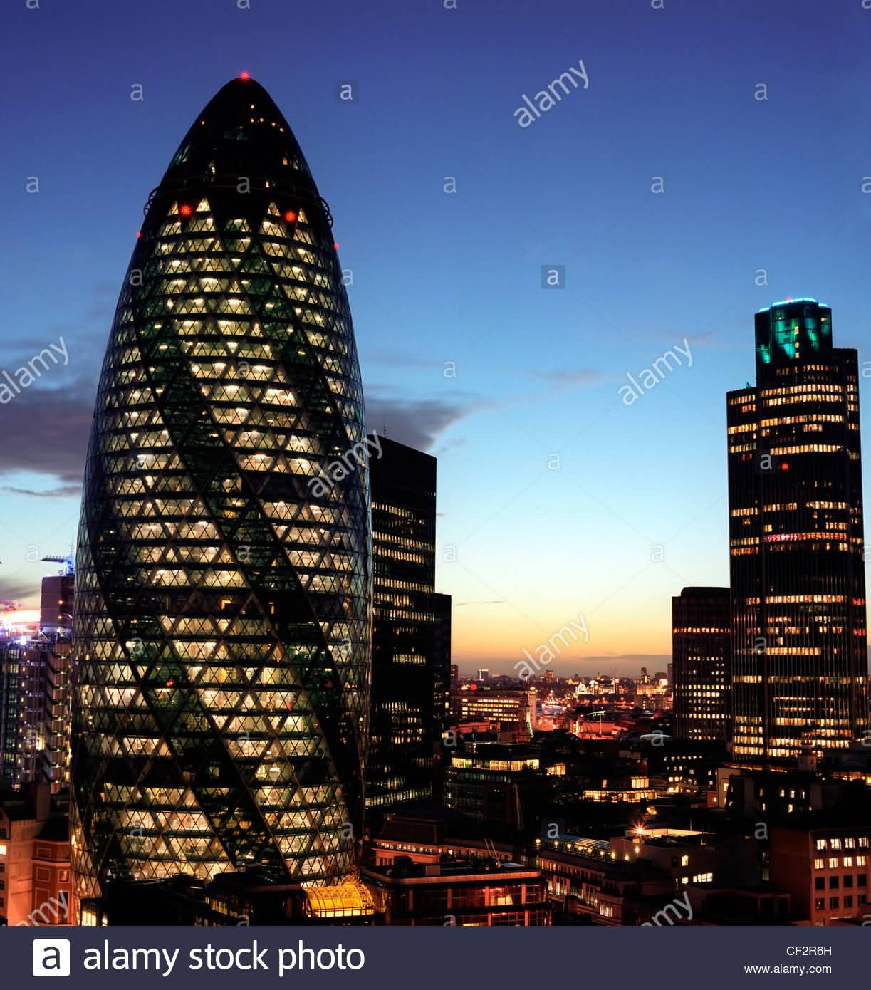 the gherkin and natwest tower buildings in london at night