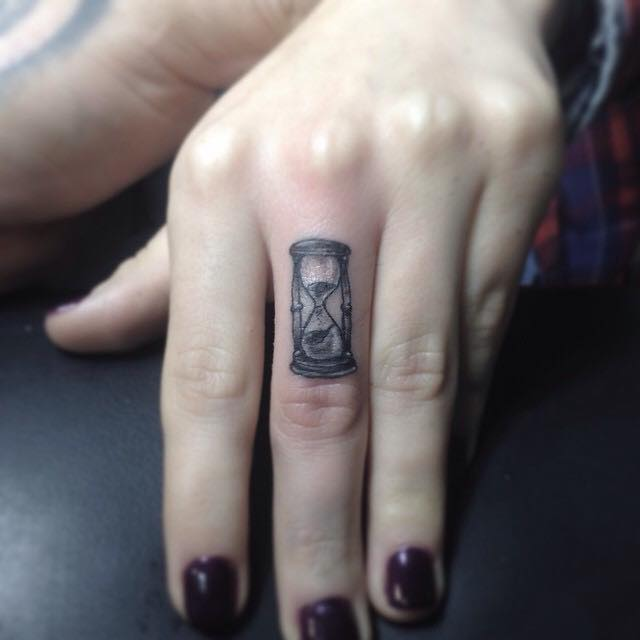 Black And Grey Hourglass Tattoo On Women Left Hand Finger