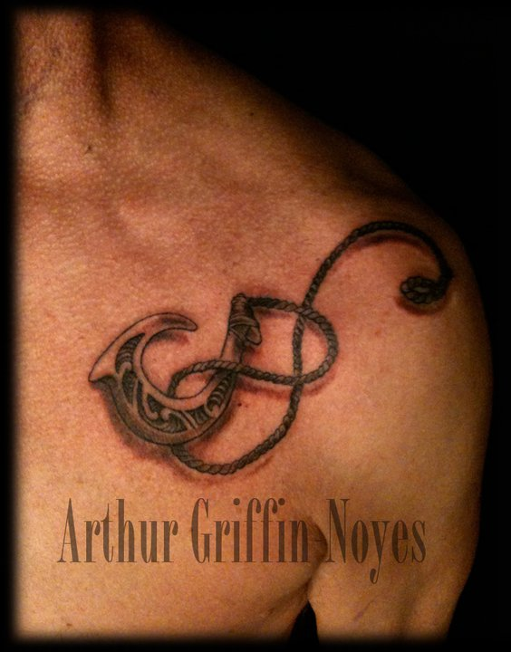 Black Ink Hook Tattoo On Man Left Front Shoulder