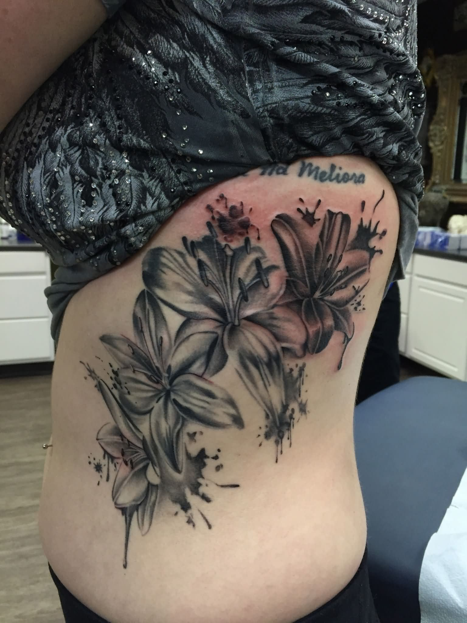 Black ink lily flowers tattoo on left side rib izmirmasajfo
