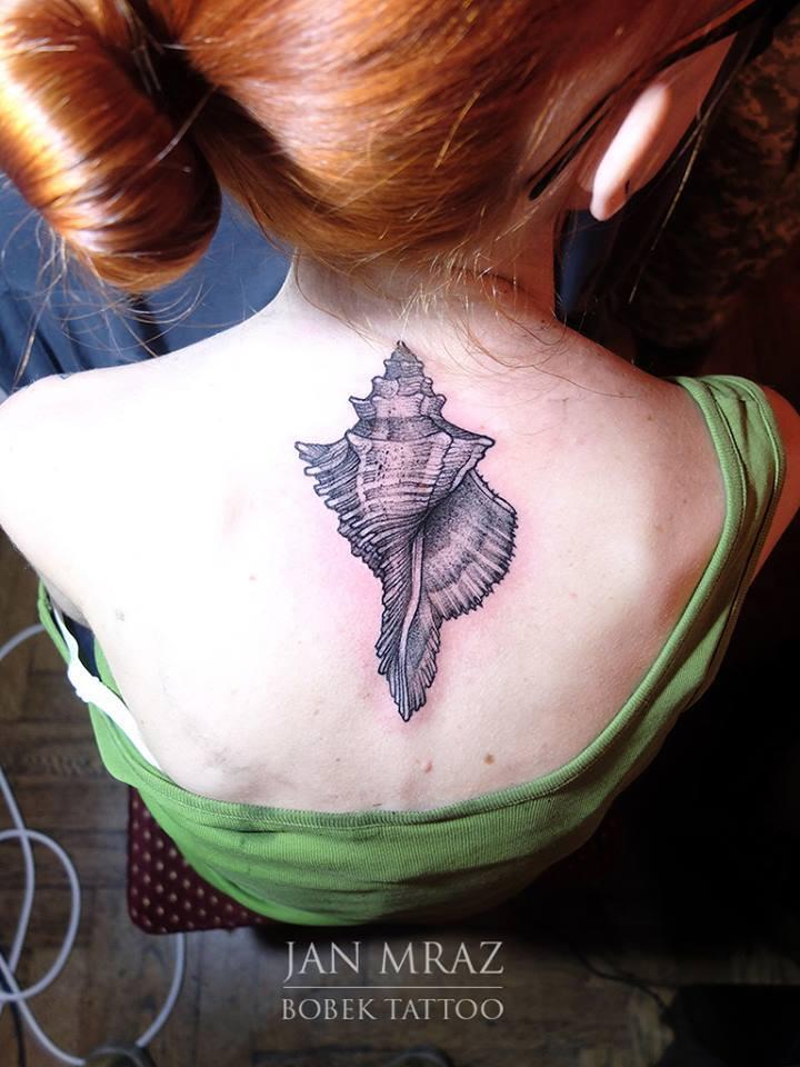 Black Ink Sea Shell Tattoo On Women Upper Back
